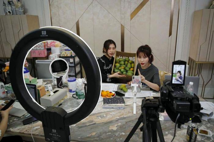 In this May 5, 2020, photo, China's online celebrity Zhang Mofan, right, introduces fresh mangos to her online clients and fans through the live-streaming at her house in Beijing.